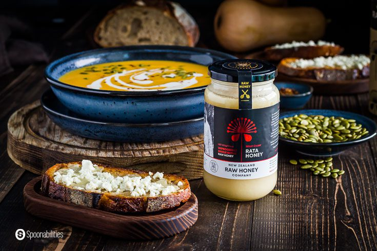 This photo has a jar of the Raw Rata Honey from New Zealand. On the left side, a Feta Honey toast on a small wooden board, and in the background, a soup bowl with butternut squash soup. Recipe at Spoonabilities.com