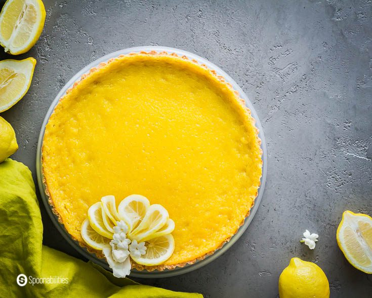 Citrus tart garnished with lemon slices. The photo is style with whole lemons and lemon halves. More about this tart recipe at Spoonabilities.com