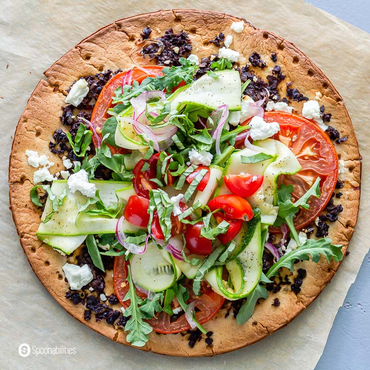 Close up of one veggie pizza with cauliflower pizza crust, Olive Bruschetta, and topped with a lot fresh vegetables. More about this recipe at Spoonabilities.com