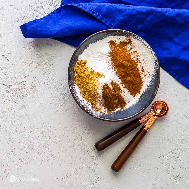 Dry ingredients in a small blue bowl for for the pistachio tiramisu: all-purpose flour, cinnamon, baking powder, ginger, nutmeg, and sea salt. Recipe at Spoonabilities