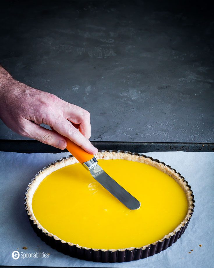 Prebake Lemon tart with a hand, smoothing out the top after pouring the lemon curd to the par-baked crust. Recipe at Spoonabilities.com