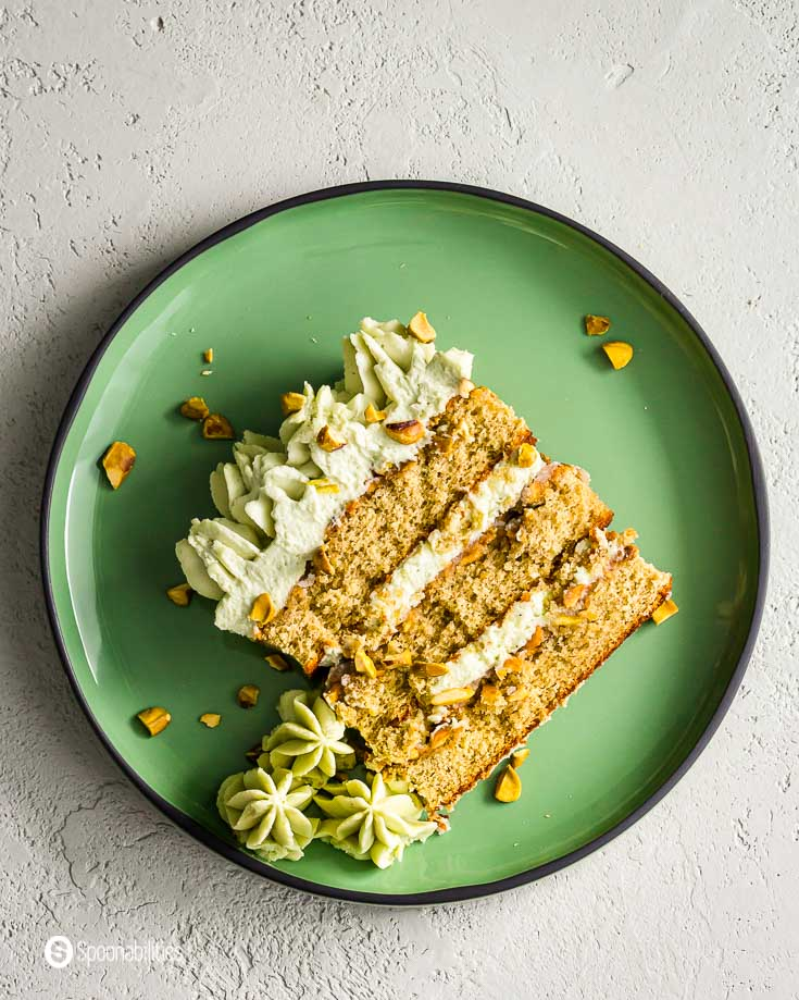 Round green plate with a slice of pistachio tiramisu cake with chopped pistachios. Recipe at Spoonabilities.com