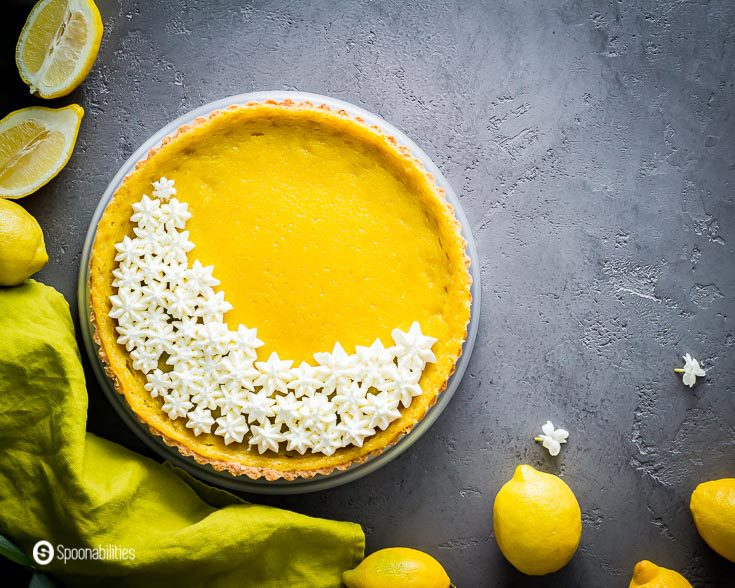 tarte au citron garnished with piped mascarpone cream. Styled with a green napkin and some lemons around the tart. Find this tart recipe at Spoonabilities.com