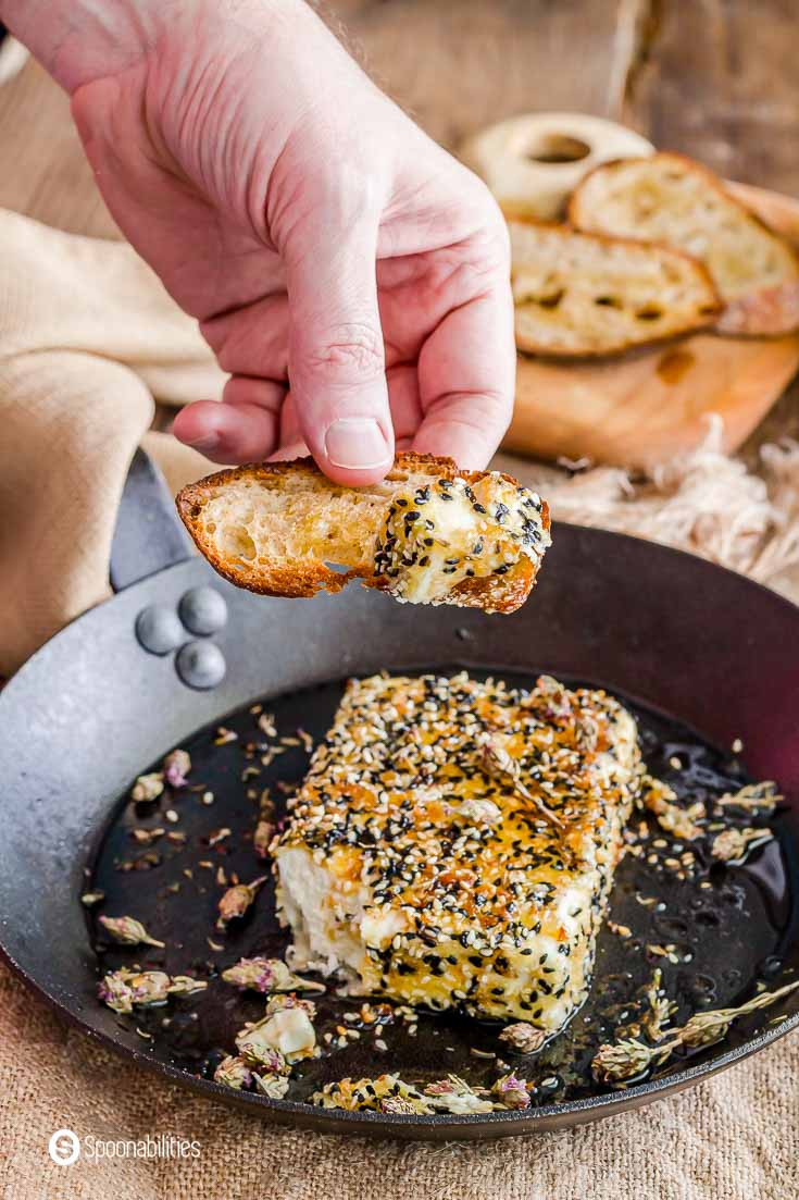 A hand with a piece of bread scooping out some of the sesame crusted fried feta cheese. Recipe at Spoonabilities.com
