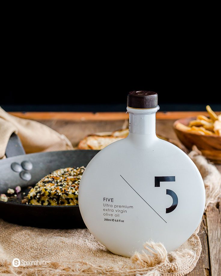 A white bottle of Five ultra premium extra virgin olive oil in front of the fry pan. Product available at Spoonabilities.com