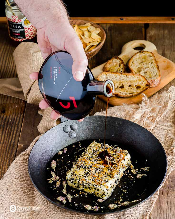 A hand pouring Five balsamic vinegar on top of the crusted pan fried feta cheese. Recipe at Spoonabilities.com
