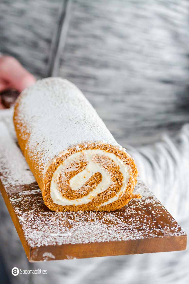 A person with a grey jacket holding the wooden board with the pumpkin cake roll and dusted with powder sugar. Recipe at Spoonabilities.com