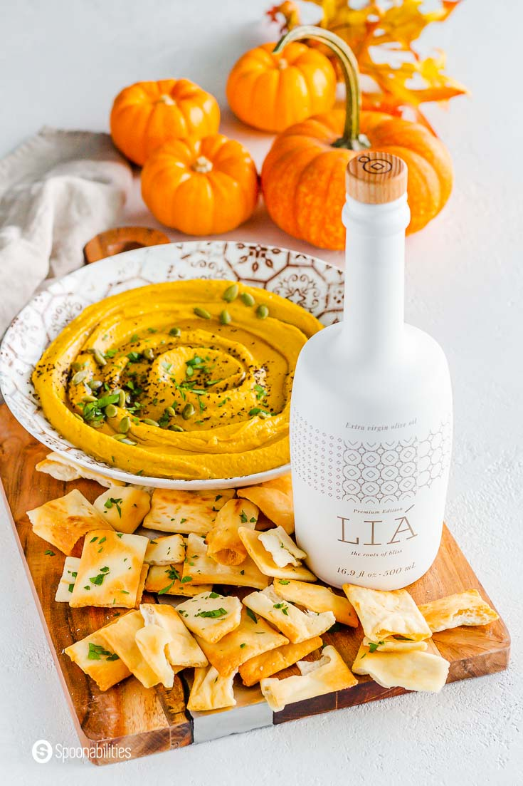 A white bottle with LIA extra virgin olive oil on top of a wooden board. Next to LIA EVOO some pita chips and in the background a large plate with pumpkin hummus and small pumpkins as a décor. Shop LIA at Spoonabilities.com