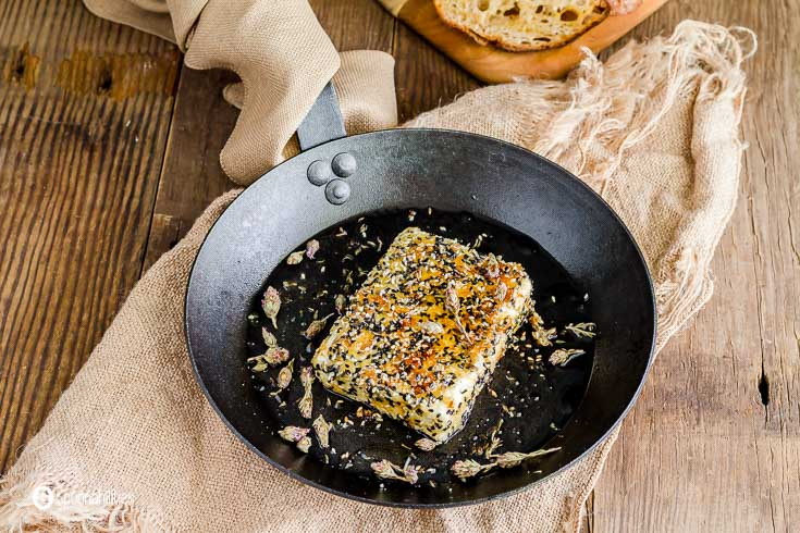 Close up photo of a pan-fried feta cheese with sesame crust garnished with thyme flowers. The pan is on top of a burlap napkin. Recipe at Spoonabilities.com