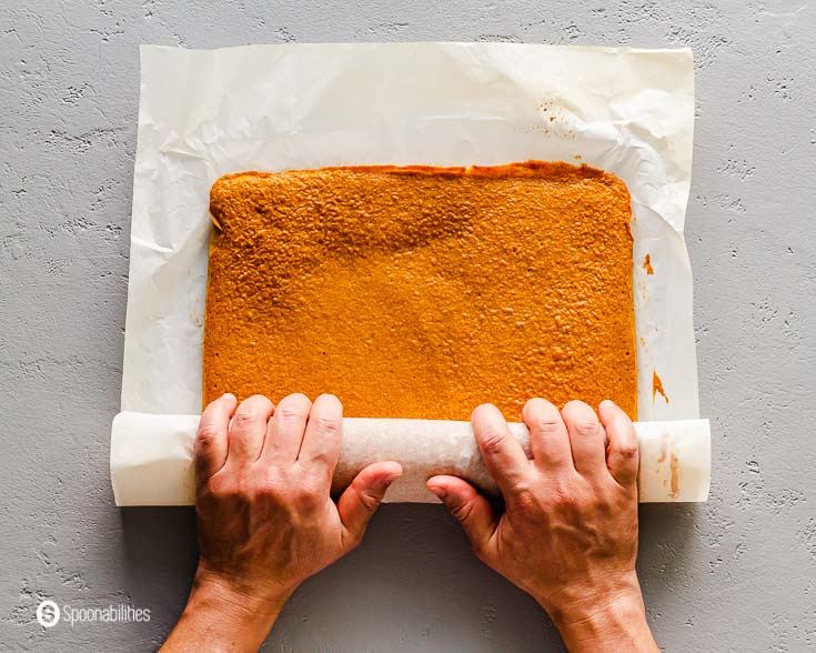Two hands are rolling up the pumpkin cake. The cake is being roll-up between the parchment paper. More details of this recipe at Spoonabilities.com