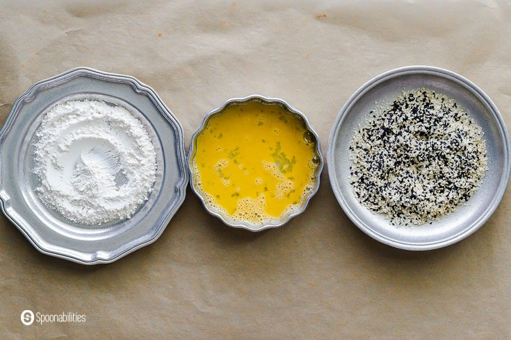 Three bowls : one with flour, the second with a beaten egg, and the last one with a mix of panko bread, white and black sesame seeds. Recipe at Spoonabilities.com