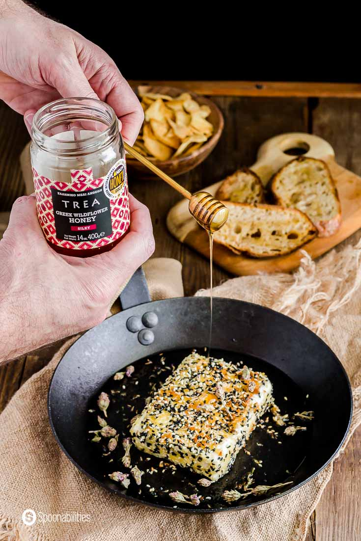 A pan with the pan seared feta crusted with sesame seeds and a hand drizzling Trea wildflower honey. Recipe at Spoonabilities.com