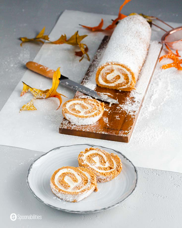 Two slices of pumpkin cake on a grey plate. In the background, the rest of the pumpkin roll on a wooden board with a piece on the board. Recipe at Spoonabilities.com