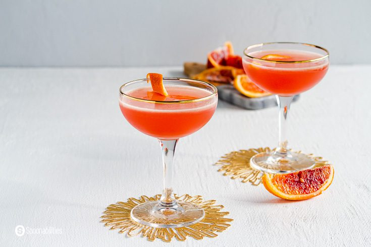 Close up of two couple glasses on top of a golden coasters. A wedge of fresh blood orange next to the glasses. In the background a cutting board with more blood orange pieces. Recipe at Spoonabilities.com