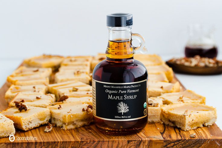 A bottle of Vermont Maple Syrup on top of an wooden board. The wooden board has a tons of Maple Cheesecake bars. Recipe at Spoonabilities.com