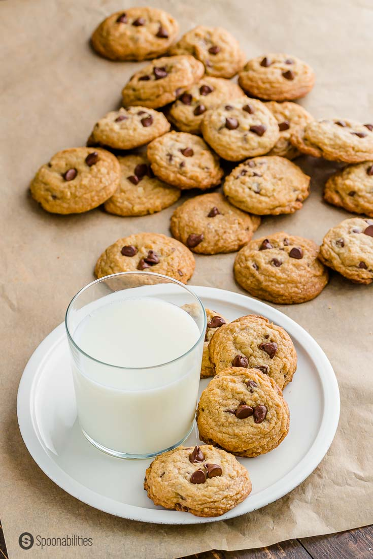 White plate with a glass of milk on top and four choc chip cookies next to the glass. The plate is on top of a brown parchment paper. Recipe at Spoonabilities.com