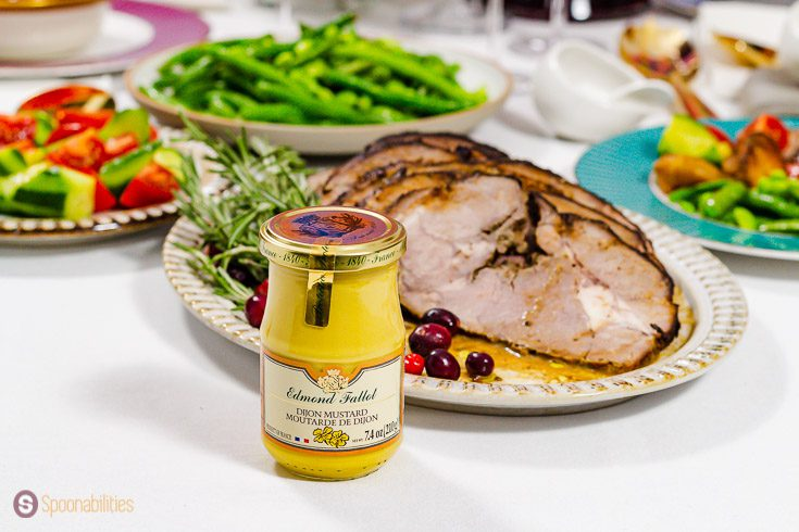 A jar of Edmond Fallot traditional Dijon Mustard in front of a oval plate with roasted lamb. Recipe at Spoonabilities.com