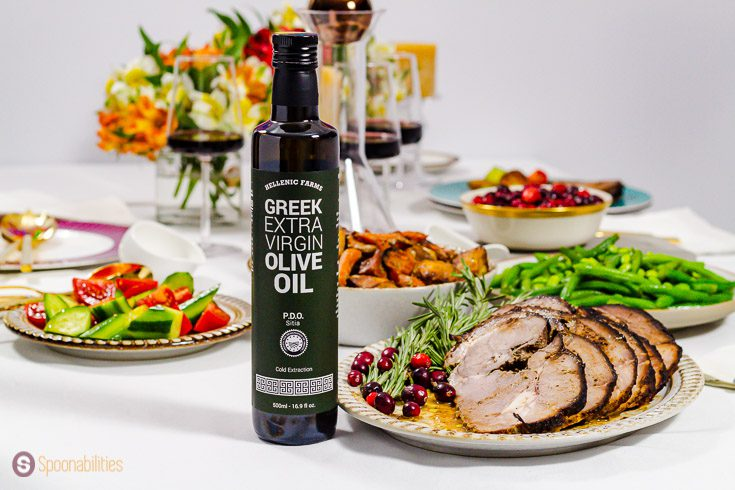 A bottle of Hellenic Farms Extra Virgin Olive oil. The bottle is in front of a plate with roasted leg of lamb garnished with fresh rosemary and fresh cranberries. Recipe at Spoonabilities.com