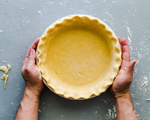 Two hands are holding the pie dish with the crust shaped. Ready to go into the refrigerator for 30 minutes. Spoonabilities.com