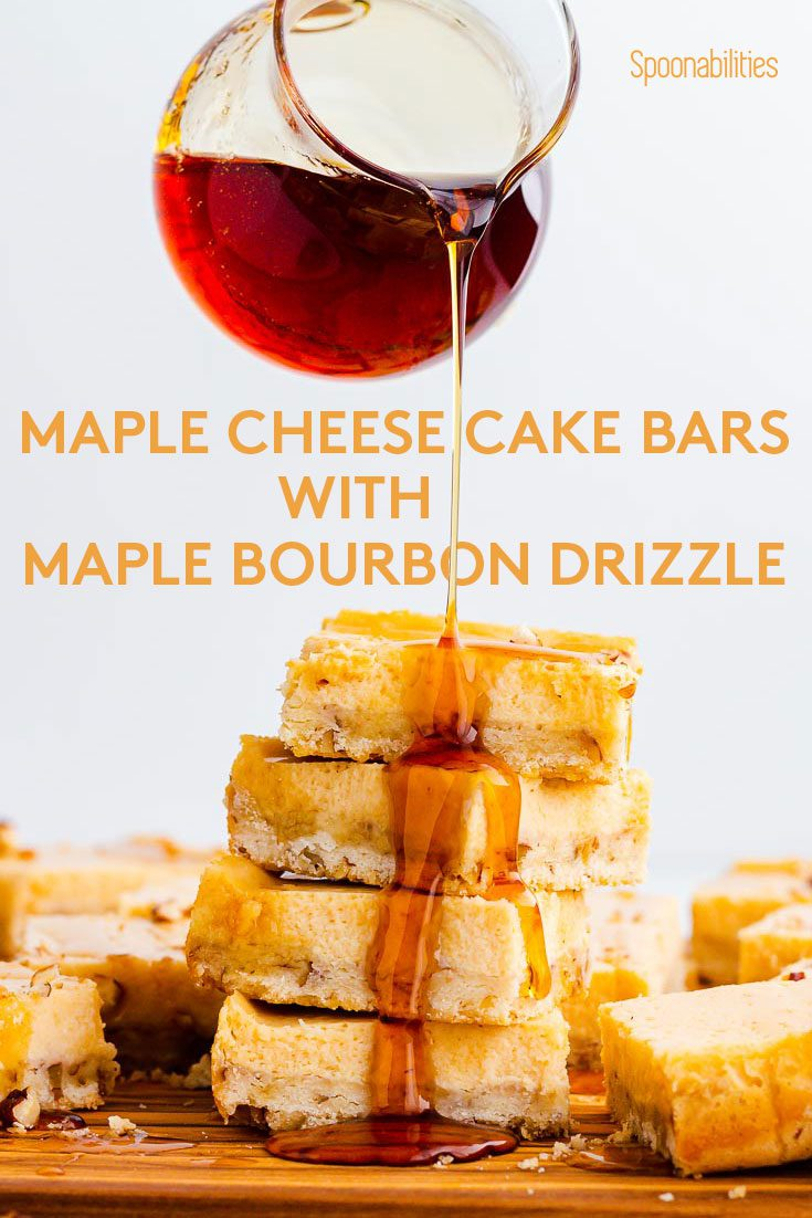 A tower of Cheesecake bars and a hand pouring Maple drizzle. The drizzle is going down as a cascade. They are four Maple Cheesecake cars on top of each other. Recipe at Spoonabilities.com