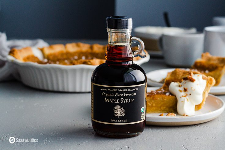 A small bottle of Maple Syrup - Grade B Dark Robust and in the background a pie dish and on the right side two small plates with a piece of the sister pie's cookbook. Recipe at Spoonabilities.com