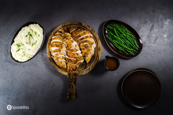 Overhead photo with three serving dishes. In the center in a wooden board the roasted turkey breast sliced, on the right side steam green beans, and on the left side mashed potatoes. Recipe at spoonabilities.com