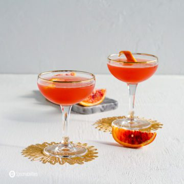 Two Coupe glasses with Solerno Cocktail . The two glasses on top of a golden coasters.