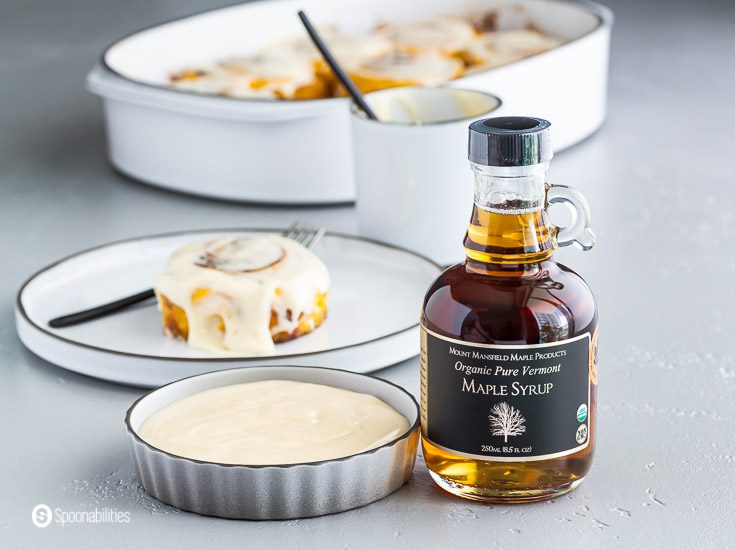 A glass botter of Organic Pure Vermont Maple Syrup and a small dish with the maple cream cheese icing on the left side. Recipe at Spoonabilities.com