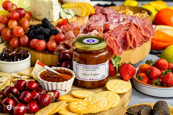 A jar of apricot preserves next to some crackers, fruits and other charcuterie food ideas. Recipe at Spoonabilities.com