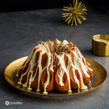 A Brandy Eggnog Bundt Cake on a large round plate with golden rim. Recipe at Spoonabilities.com