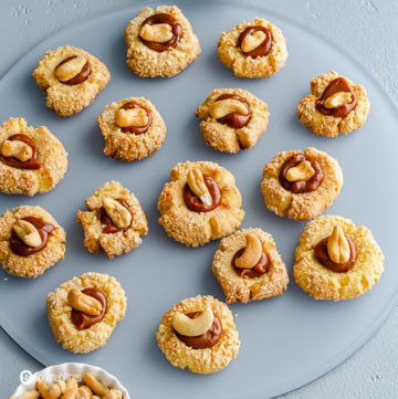 Close-up of the Cashew Thumbprint cookies on a frosted plate. Recipe at Spoonabilities.com