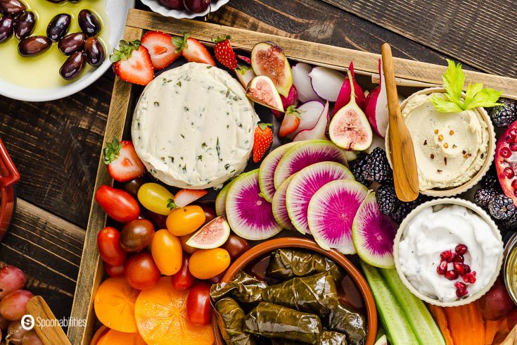 Wooden tray with cashew milk cheese with chives, dolma, plant-based tzatziki dip, cashew dip with roasted garlic, and fruits and vegetables. Recipe at Spoonabilities.com