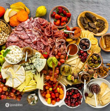 Overhead photo of a grazing table with a charcuterie board, cheeseboard, and gourmet products. Read more Charcuterie Board Ideas at Spoonabilities.com