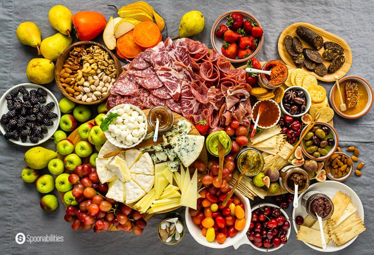 Overhead photo with an impressive grazing table with a complete charcuterie board, cheeseboard, and gourmet products. Read more Charcuterie Board Ideas at Spoonabilities.com