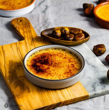 A grey ramekin on top of a wooden board and garnished around some pilled chestnuts in a small wooden pinch bowl. The ramekin has Chestnut Crème Brûlée. Recipe at Spoonabilities.com