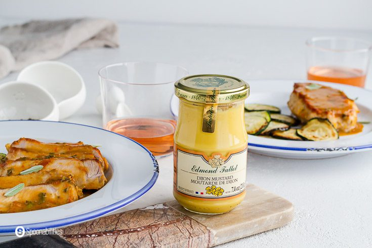 a jar of Edmond Fallot Dijon Mustard between two white plates with pan-seared pork chops with apricot Dijon mustard sauce and zucchinis. Available at our shop at Spoonabilities.com