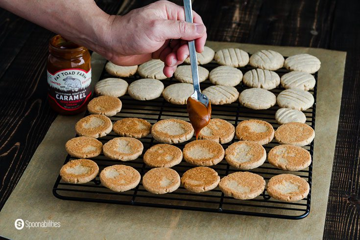 Cookies in a cooling rack and a hand with a spoon with goat's milk caramel sauce is filing the cookies with the sauce. Recipe at Spoonabilities.com
