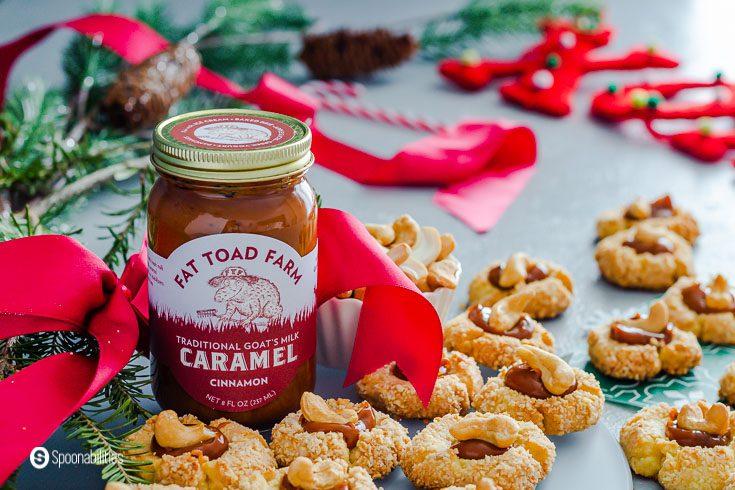 A jar of Cinnamon Goat's milk caramel sauce (Cajeta) with some thumbprint cookies around the jar filled with caramel sauce and a whole cashew on top. The jar is with a red bow. Recipe at Spoonabilities.com