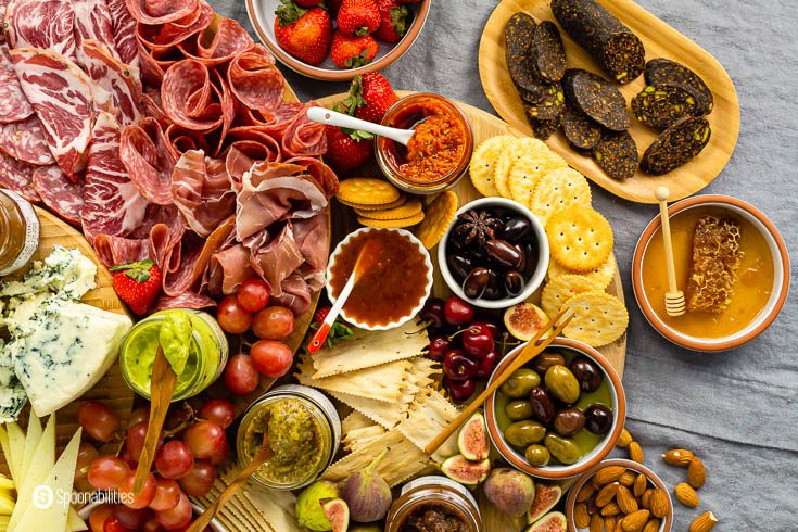 Overhead photo with some olives, jams, and other spreads in a wooden board. Charcuterie Board Ideas Recipe at Spoonabilities.com