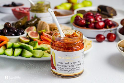 A open jar of sweet red pepper and graviera cheese spread from Hellenic Farms. The jar has a white spoon inside. In the background a large plate with some mezze dishes. Product available at Spoonabilities.com