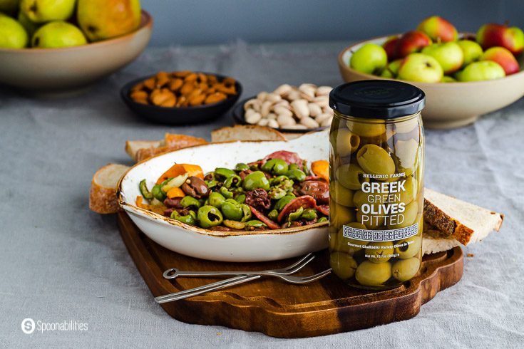 A jar of Green green olives on a wooden tray and in the background a plate with marinated olives, a bowl of apples, pears, nuts, and bread. Recipe at Spoonabilities.com
