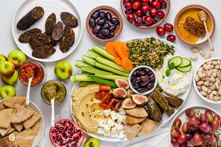 A large spread of delicious mezze dishes along with fruits and vegetables. Recipe at Spoonabilities.com