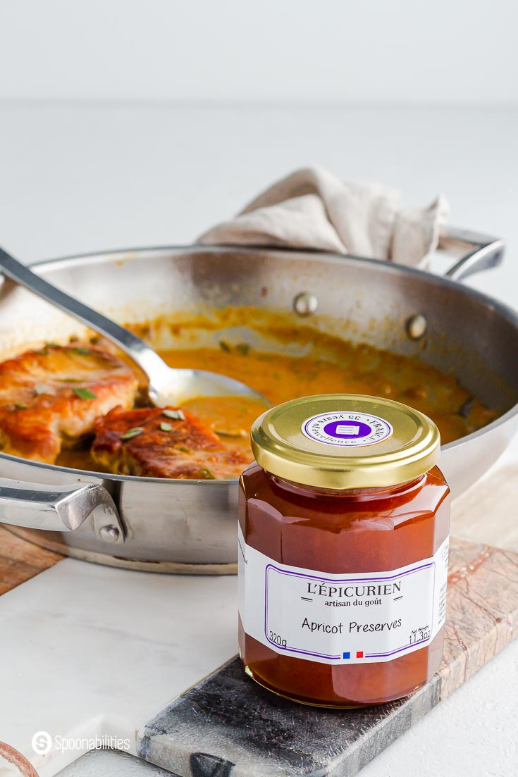 A close up photo of L'Epicurien Apricot Preserves jar. The jar is on top of a marble board and in the background a sauté pan with two pork chops and one spoon. Available at our shop at spoonabilities.com