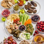 An oval white plate with different Greek appetizers, vegetables, fruits, and spreads. Recipe at Spoonabilities.com