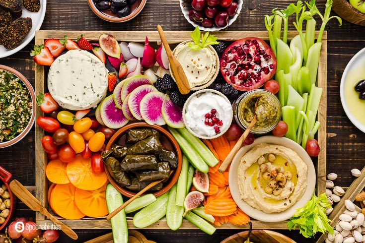 A close up photo from overhead to the Mediterranean Vegan mezze platter. The platter has fruits, vegetables, dips, vegan dips and spreads, and more. Recipe at Spoonabilities.com