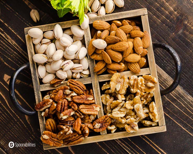 A wooden tray with almonds, walnuts, pistachios, and pecan. Recipe at Spoonabilities.com