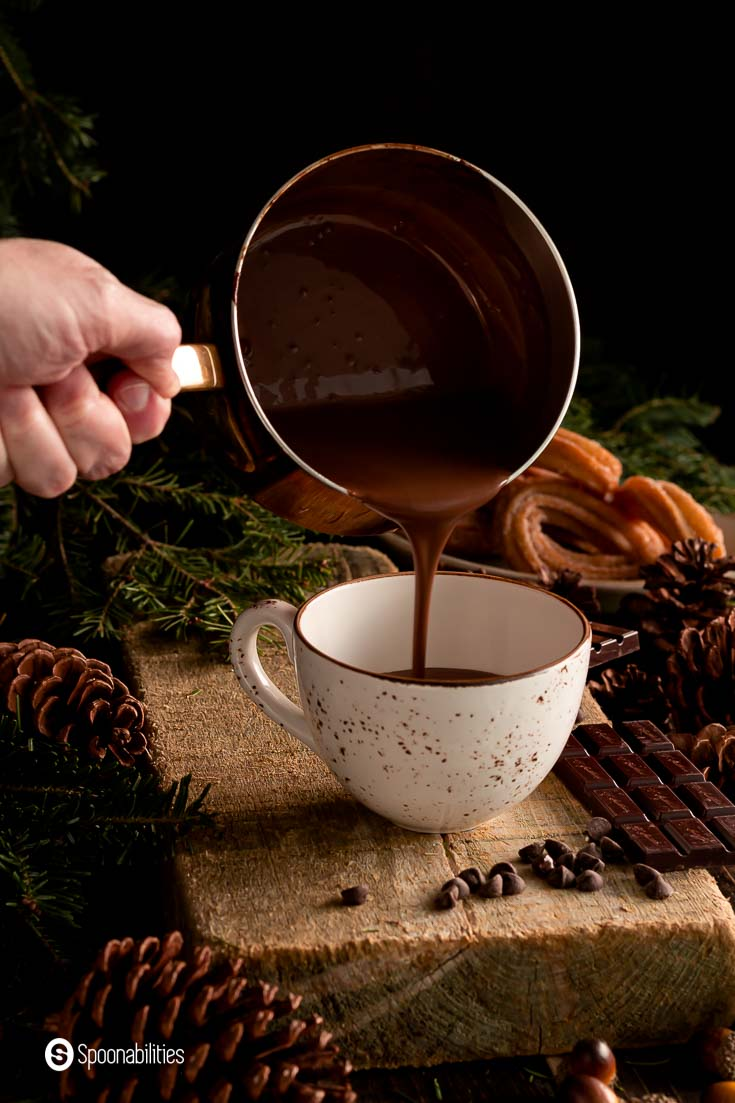 Pouring Spanish hot chocolate into a mug. The mug is on top of a wooden block and around the mug is decorate with a cozy holiday décor. Recipe a Spoonabilities.com