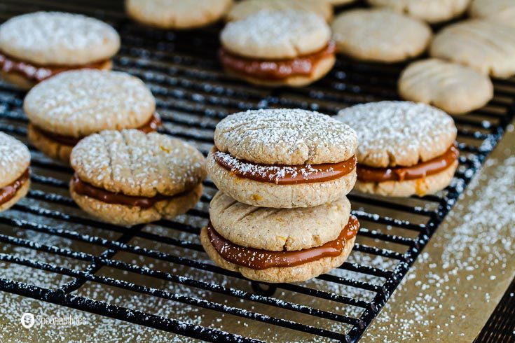 Black wire cooling rack with shortbread cookies filled with Goat's milk caramel sauce flavored with Irish Whiskey cream. The main cookies are in the center of the photo with two sandwiches cookies on top of each other. Recipe at spoonabilities.com