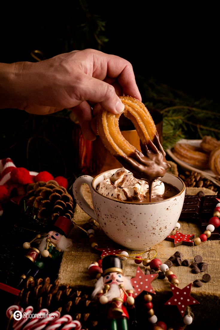 A cozy mug with hot chocolate and a hand dipping a churros into the Spiced Spanish Hot Chocolate. Recipe at Spoonabilities.com