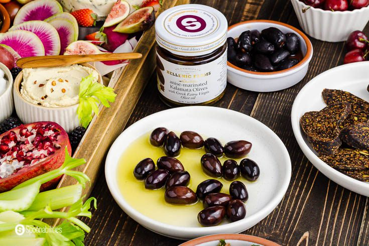 A jar of Kalamata olives marinated in anise and other Mediterranean spices. In front of the jar a small plate with the olives and olive oil from the marinated. Product at Spoonabilities.com